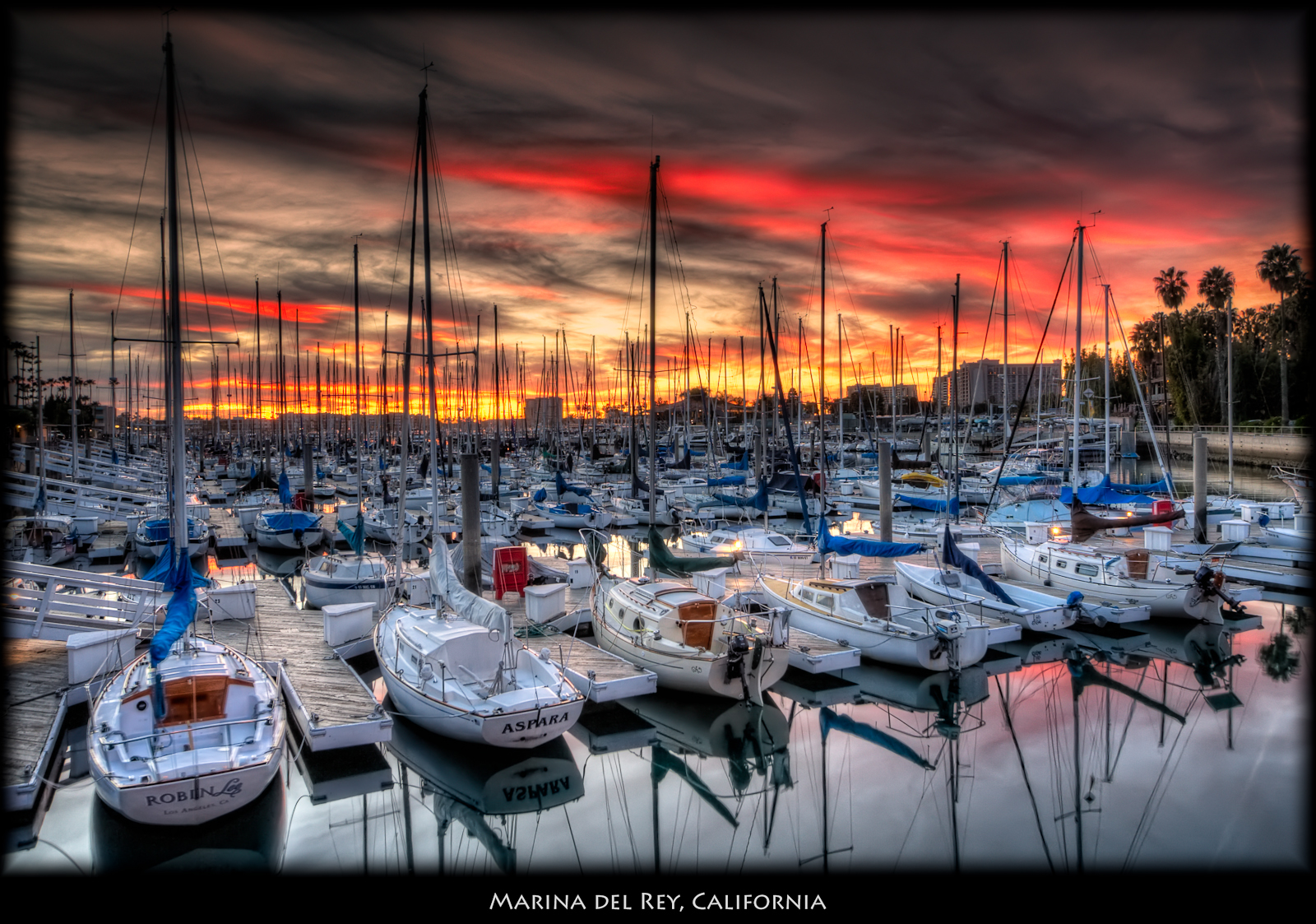 This is the time of year for nice sunsets in Los Angeles. I finally got out with my camera an HDR sequence of this sunset. I wanted the boats to be clearly visible, but still have the sunset colors. I tried using f18, but even though there was no wind, the boats do move quite a bit, and Photomatix did a poor job of blending. I discovered that if you tell Photomatix to adjust for moving objects the quality is much lower than if you just ask for adjusting for background movement. So, for this shot I used the f5.6, and didn't get the nice starburst for the lights that had come on. ISO 100, 16mm, f5.6, (1/25, 1/6, 0.6 secs) Used Photomatix details enhancer to produce an image with very few shadows (low smoothness). In Nik added Tonal Contrast on the boats, Pro Contrast, a Coffee Graduated Filter with small opacity. Used Viveza to add a bit of brightness and contrast to the reds because I remembered being struck by how bright the reds were when I was out there.