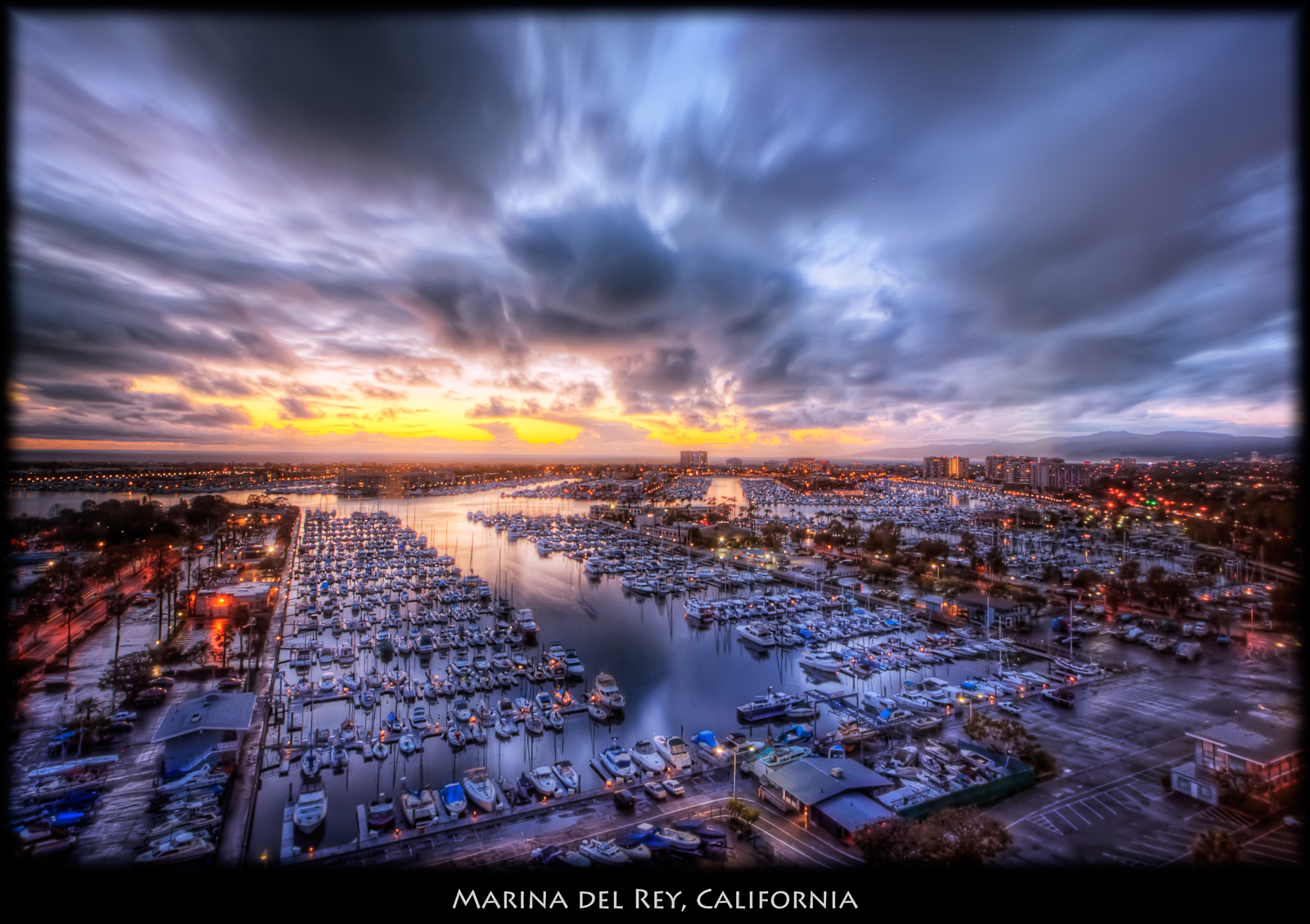 View of the marina from my office when the sun had gone down and the lights started to get turned on. ISO 200, 11mm, f7.1, 8 exposures. HDR build using Photomatix, and tonemapped using Details Enhancer. Imagenomic noise reduction, Nik Pro Contrast and Remove Color Cast to try to neutralize the purple cast created by the energy conservation film on our windows. Curves in PS and slight blurring to tame some of the tonemapping on the clouds.
